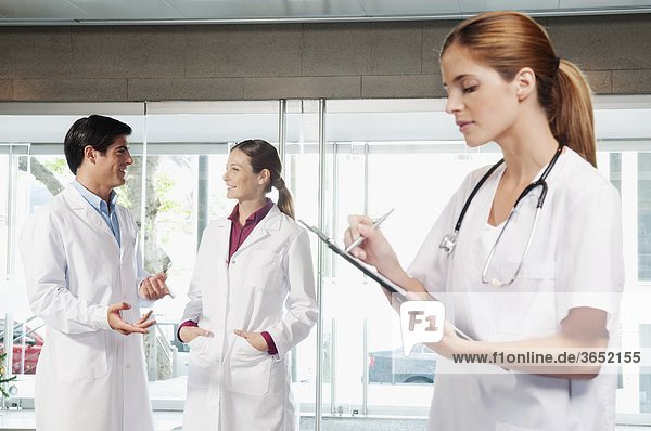 Female nurse writing on a clipboard with her colleagues discussing in the background
