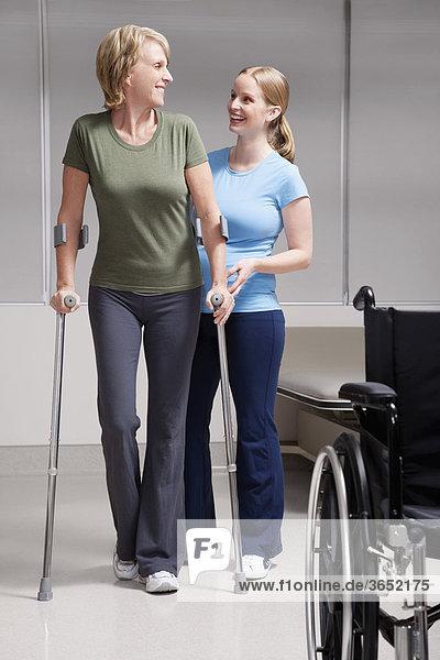 Physiotherapeut bei Patienten mit Krücken gehen