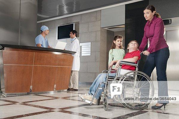 Frau schieben ihren Sohn im Rollstuhl