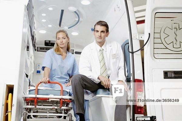 Arzt sitzen mit einem weiblichen Krankenschwester in einen Krankenwagen