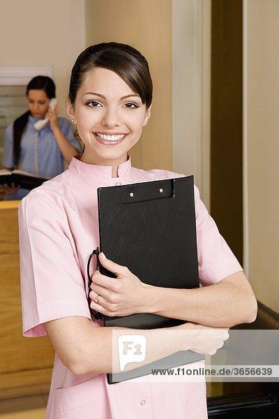 Porträt einer Ärztin hält eine Zwischenablage und lächelnd