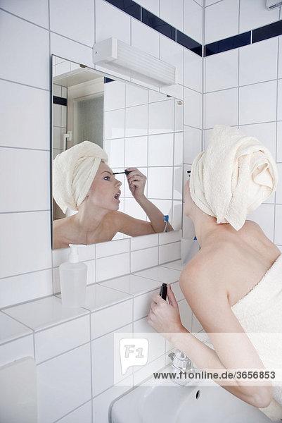 Frau beim Tuschen der Wimpern im Bad vor dem Spiegel
