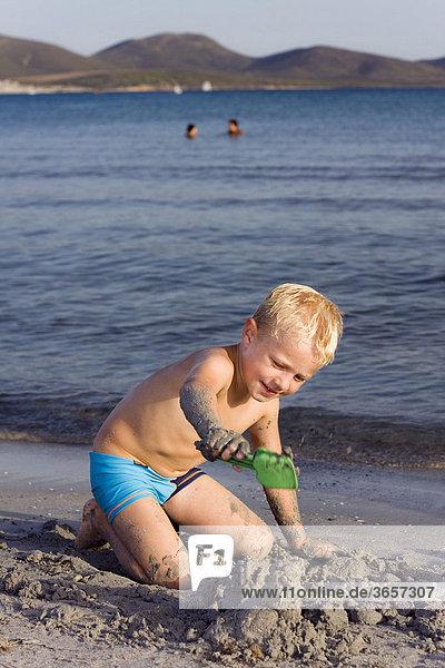 Ein Junge  5 Jahre  an einem Sandstrand  buddelt im Sand