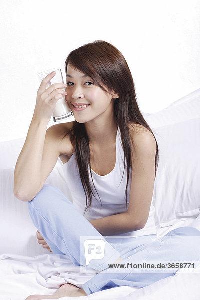 Junge Asiatin mit einem Glas Milch