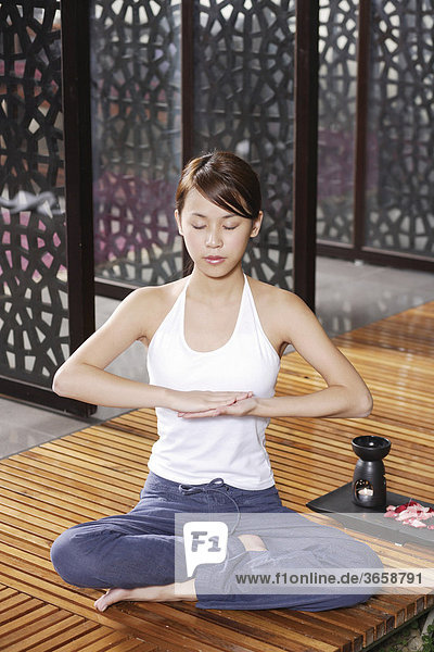 Junge Asiatin beim Yoga