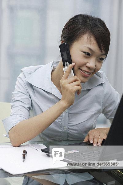 Eine junge Frau telefoniert im Büro