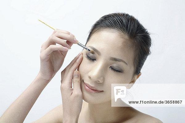 Junge Asiatin schminkt sich
