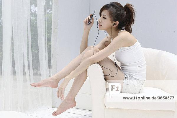 Junge Asiatin hört Musik in einem Sessel
