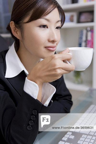 Geschäftsfrau beim Kaffeetrinken im Büro