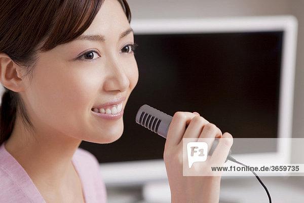 Junge Frau beim Karaoke