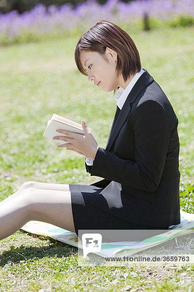 Geschäftsfrau liest im Park