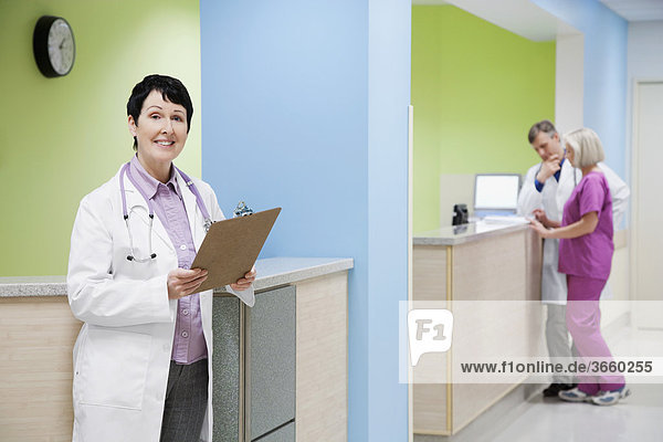 Female doctor holding a clipboard with a doctor and nurse in the background