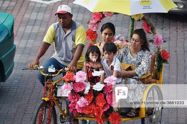 Malacca (Malaysia): a Malay mother and her children touring around the city on a rickshaw in the Town Square