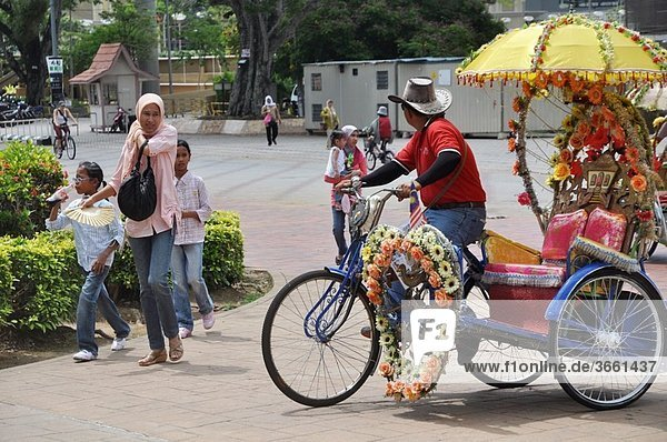 Malacca (Malaysia): a rickshaw driver offering his service to a family by the Porta de Santiago