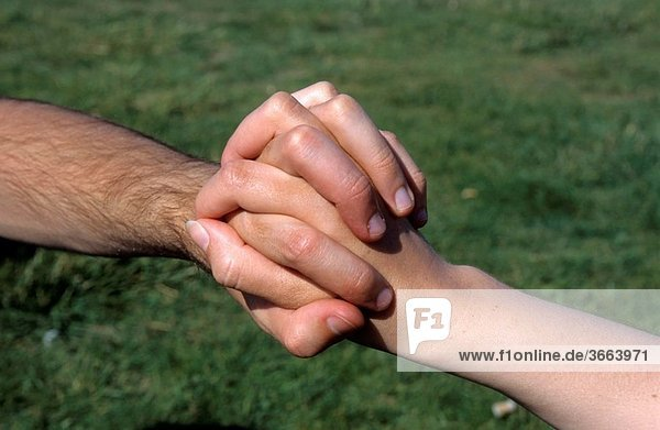 Man and woman s hands holding tight together