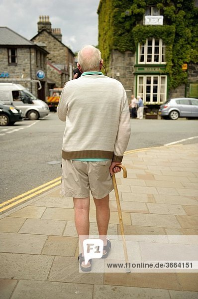 Rear view of an elderly man walking with the aid of a stick in Dolgellau  UK