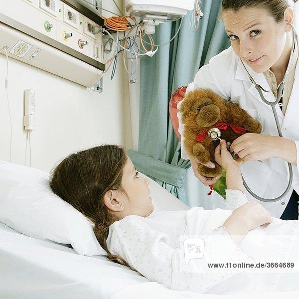 Mädchen auf einem Krankenhausbett mit einem weiblichen Arzt untersuchen ein Stofftier