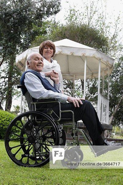 sitzend stehend nebeneinander neben Seite an Seite Portrait Frau Mann Rollstuhl