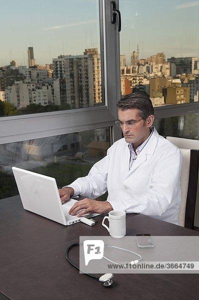 Arzt auf einem Laptop arbeiten