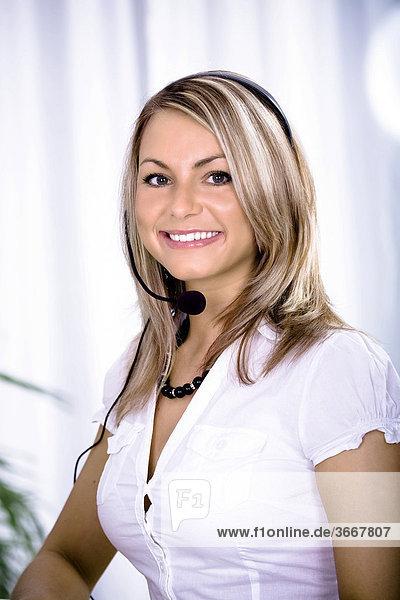 Junge Frau mit Headset  als Operator einer Hotline