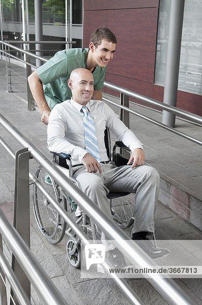 Male nurse pushing a man in wheelchair