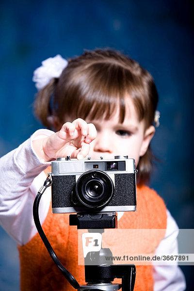 Kleines Mädchen mit alter Fotokamera