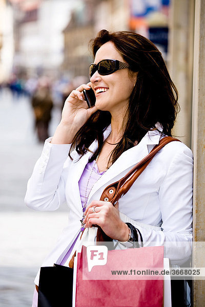 Young woman with shopping bags speaking on the phone in the street