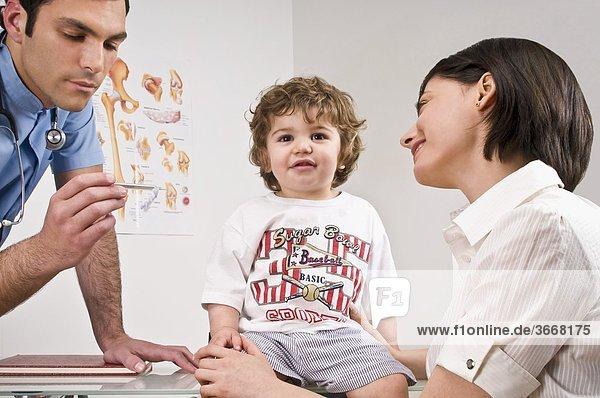 Arzt lesen einen Baby-jungen Temperatur sitzend mit seiner Mutter