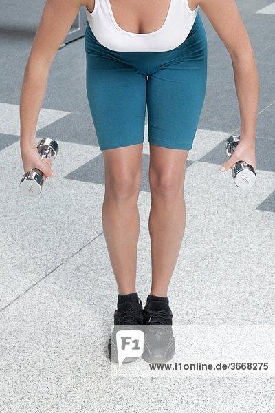 Frau beim training mit Hantel in einer Turnhalle