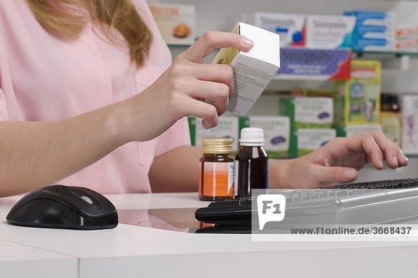 Female Pharmacist halten ein Medikament in einer Apotheke