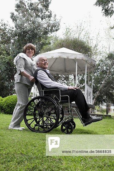 sitzend Frau Mann schieben Rollstuhl