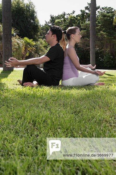 Paar Übendes Yoga in einem park