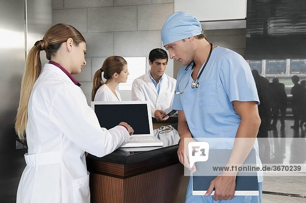Mit einem Laptop mit ständigen neben ihr Chirurg ärztin