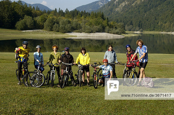Group of mountainbikers with their bikes at a mountain lake Loedensee near Reit im Winkl Upper Bavaria Germany