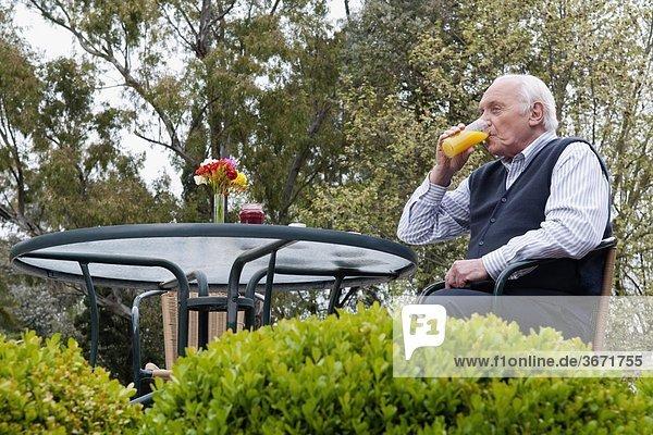 sitzend Senior Senioren Mann Stuhl trinken Saft