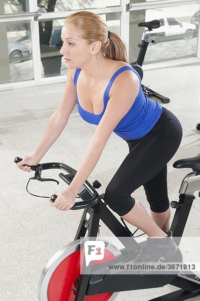 Woman working out on an exercise bike in a gym