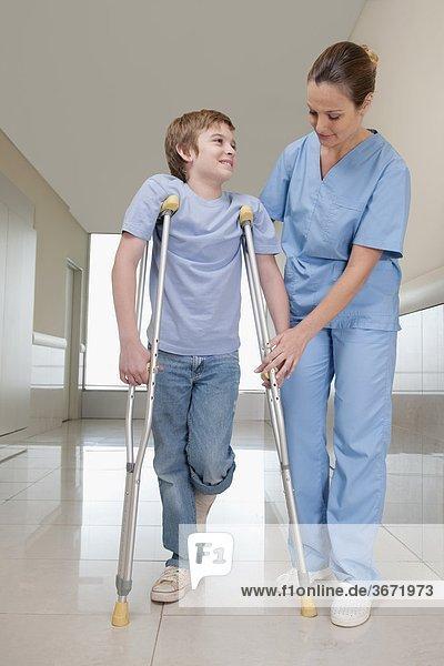 Arzt zur Unterstützung eines Patienten zu Fuß