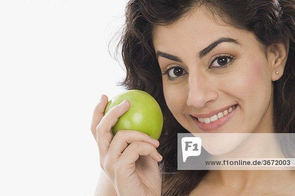 Portrait einer Frau hält einen grünen Apfel und lächelnd