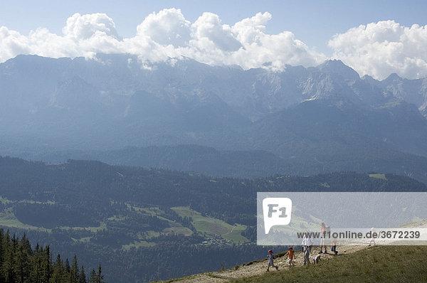 Wanderer Bergsteiger auf dem Wank bei Garmisch-Partenkirchen Blick auf die Zugspitze und das Wettersteingebirge Oberbayern Deutschland