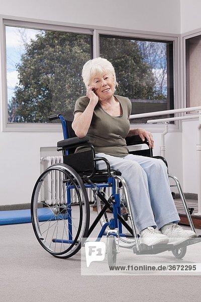 Handy sitzend Frau sprechen Kurznachricht Behinderung Rollstuhl