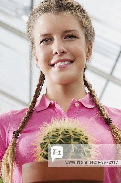 Frau halten Topfpflanze Kaktus Treibhaus