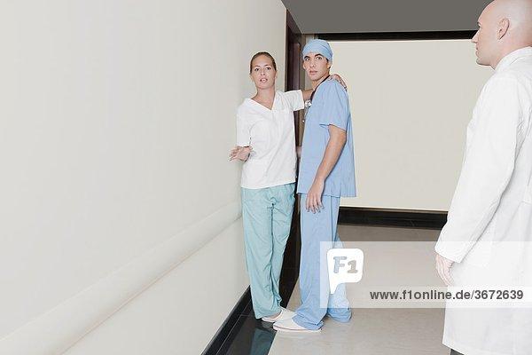 Männlich flirtet mit weiblichen Krankenschwester im Korridor krankenhaus krankenschwester