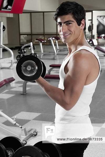 Portrait of a man exercising with dumbbell in a gym