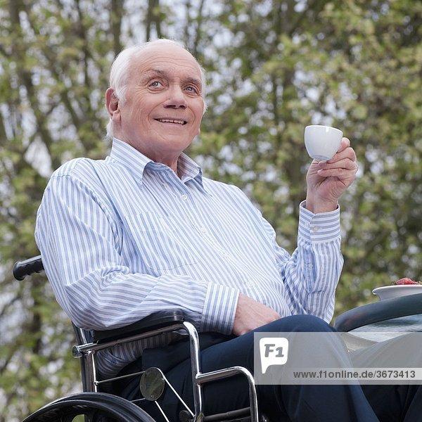 sitzend Mann trinken Tee Rollstuhl