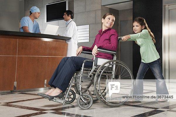 Frau sitzen im Rollstuhl durch ihre Tochter geschoben