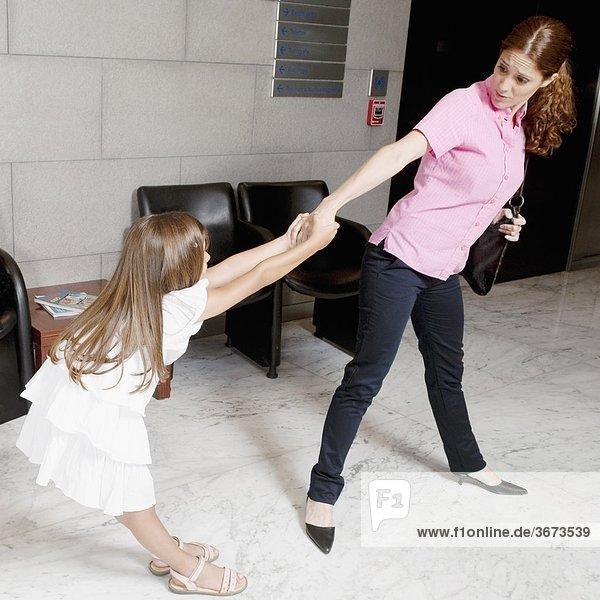 Mädchen ziehen ihre Mutter Hand in einem Krankenhaus