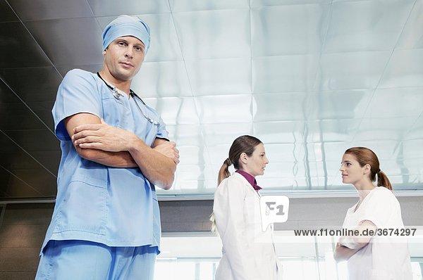 Männlich Chirurg steht mit seinen Kollegen diskutieren im Hintergrund