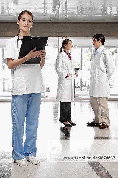 Ärztin mit ihren Kollegen im Hintergrund