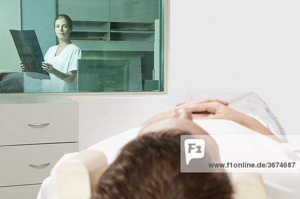 Patient durchlaufen ein MRI Scan mit einem Arzt analysieren einen x-ray-Bericht im Hintergrund