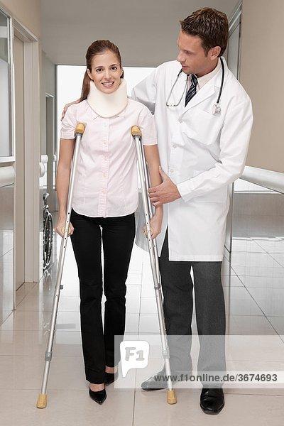 Arzt zur Unterstützung eines Patienten zu Fuß in einem Korridor Krankenhaus